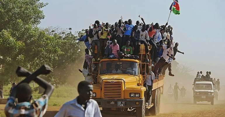 Residents hang from a bus and hold a South Sudanese flag in the disputed Abyei region of Sudan. - Source: ALI NGETHI/AFP via Getty Images