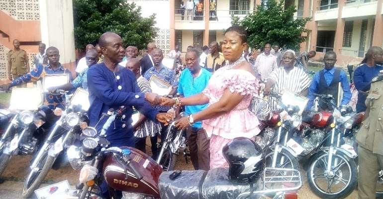 Hon. Kena handing the bikes over to the PM, Hon.Kate Mawusi