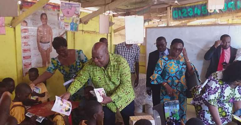 The Greater Accra Regional Minister, Hon. Ishmael Ashitey Distributing the Books to the School Children