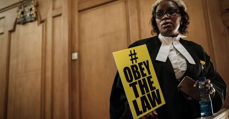 Law Society of Kenya official Mercy Wambua holds a placard at the Supreme Court in Nairobi after a protest over government disobedience of court orders.  - Source: Yasuyoshi Chiba/AFP via Getty Images