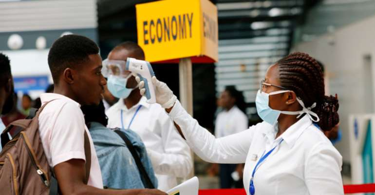 File: A health worker checks the temperature of a traveller as part of the coronavirus screening procedure at the Kotoka International Airport in Accra.