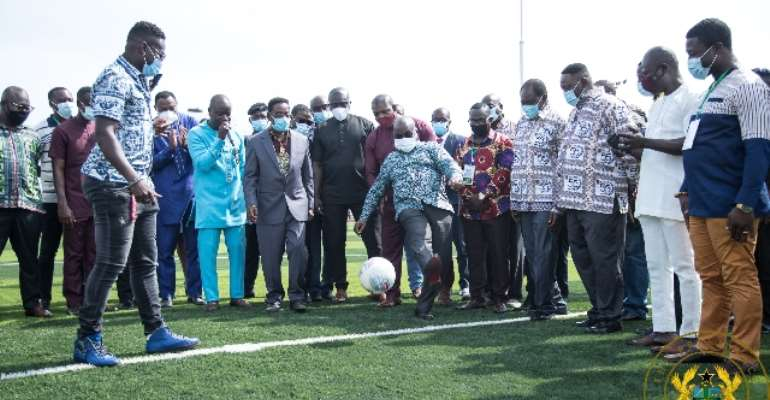 President Akufo-Addo kicks a football as he commissions the AstroTurf facility at UPSA