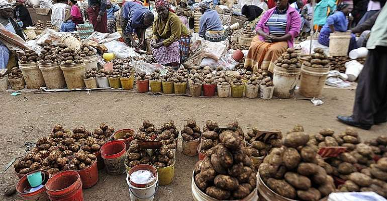 Vendors sell potatoes in a street market on the outskirts of Nairobi.  - Source: SIMON MAINA/AFP via Getty Images