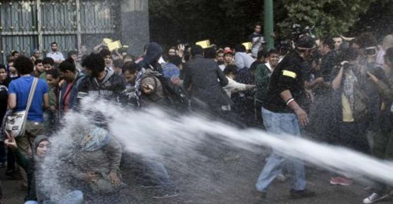 Egyptian policemen use a water canon to disperse protesters during a demonstration organized by the group