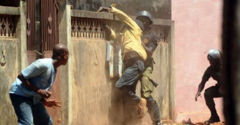 A man is caught by a policeman during a demonstration in Conakry to demand transparency in elections.  By Cellou Binani (AFP)