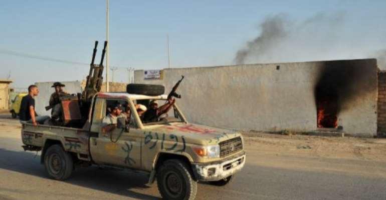 Libyan rebels drive through a street after defeating loyalist troops in Al-Jamil in 2011.  By Carl de Souza (AFP/File)