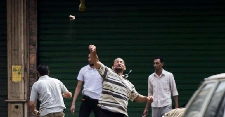 A supporter of ousted president Mohamed Morsi throws stones, in Cairo, on August 13, 2013.  By Gianluigi Guercia (AFP)