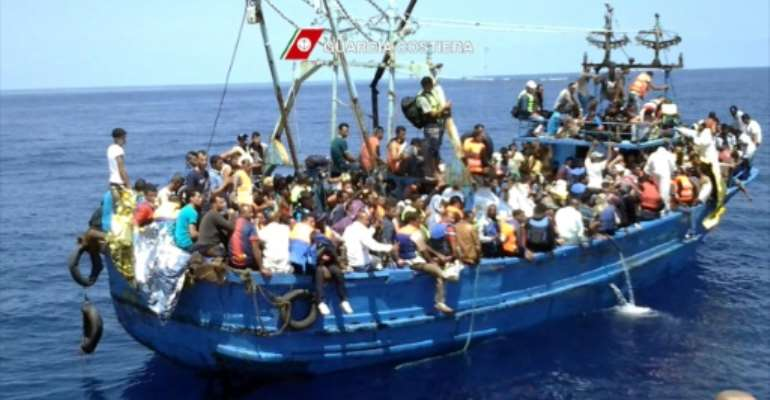 Migrants wait on an overcrowded boat on August 23, 2015 during a rescue operation by Italian coast guards off the coast of Libya.  By  (Guardia Costiera/AFP)