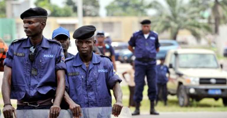 Police officers stand watch at a march in Kinshasa on February 16, 2013, to protest against the rule of President Joseph Kabila, in spite of a ban.  By Junior D. Kannah (AFP/File)