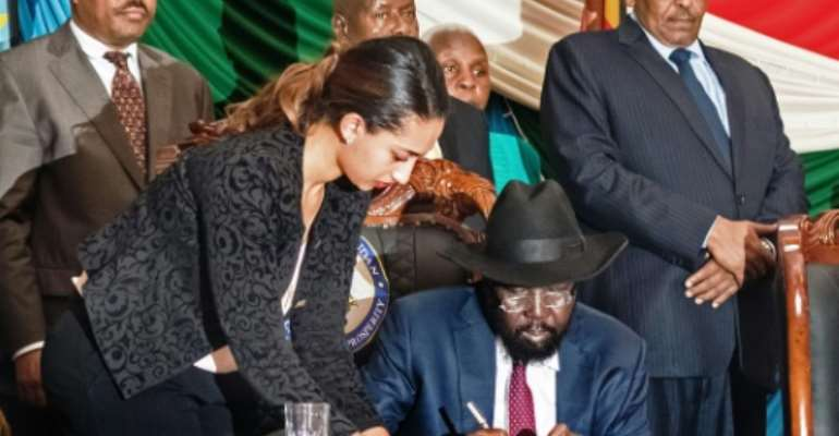 South Sudan's President Salva Kiir (C) signs a peace agreement in Juba on August 26, 2015, designed to end 20 months of civil war.  By Charles Lomodong (AFP)