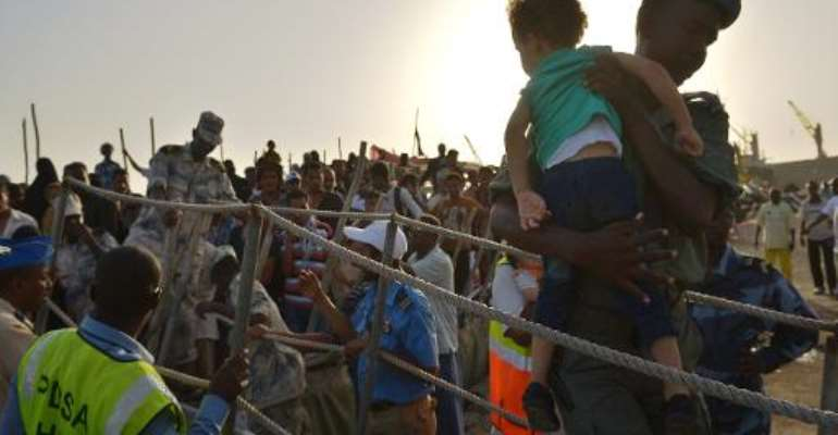 A Djibouti security official carries a young girl down a gangway as people fleeing Yemen arrive aboard a dhow on April 14, 2015 at a the port of Djibouti.  By Tony Karumba (AFP/File)
