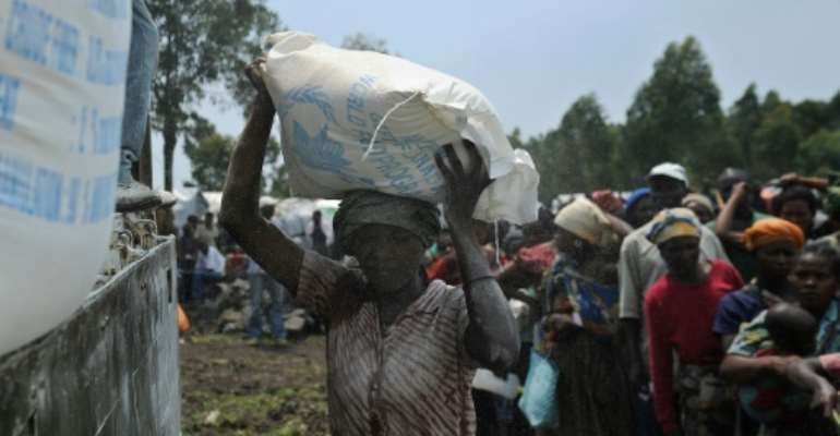 A displaced Congolese woman volunteers to offload sacks of maize-flour during a food aid distribution at a camp for the internally displaced in Mugunga, on  November 24, 2012.  By Tony Karumba (AFP/File)