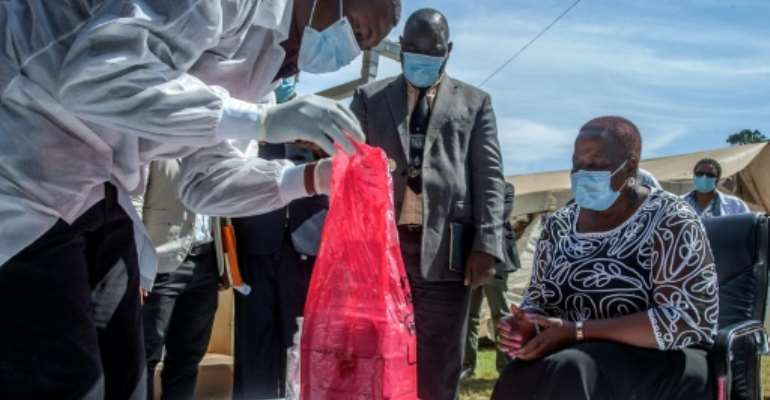 A batch of AstraZeneca from the AU had just a two-week shelf life, Health Minister Kumbize Kandodo, right, noted as the doses were incinerated.  By Amos GUMULIRA (AFP)