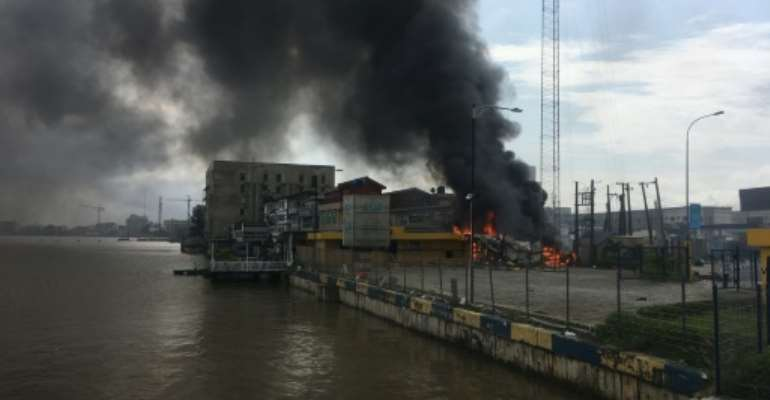 A building burns near the Lekki toll gate, epicentre of the Lagos protests.  By SOPHIE BOUILLON (AFP)
