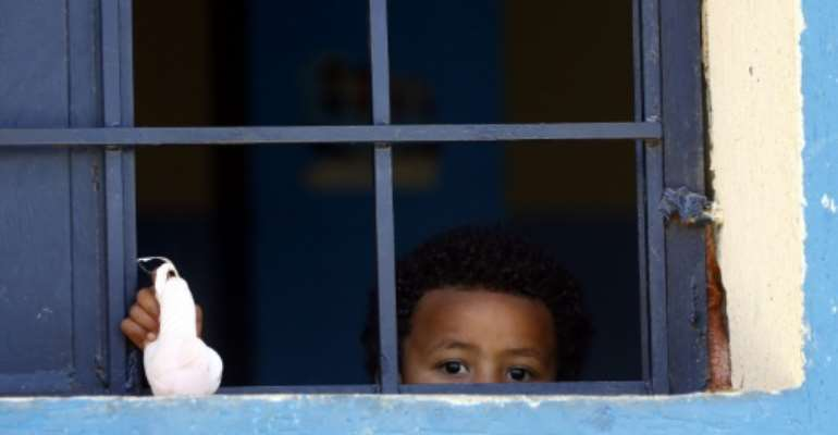 A child from a family of African migrants peeks out from a window at Libyan detention center, among thousands who have tried in recent years to flee to Europe via the North African country.  By Mahmud TURKIA (AFP)