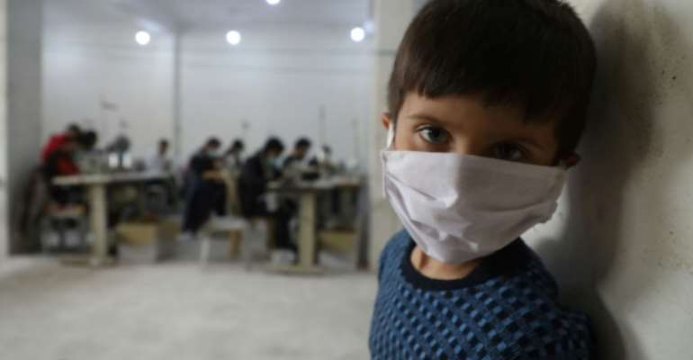 A child looks on as volunteers gather in a sewing workshop to make protective face-masks in the northeastern Syrian city of Idlib.  By AAREF WATAD (AFP/File)