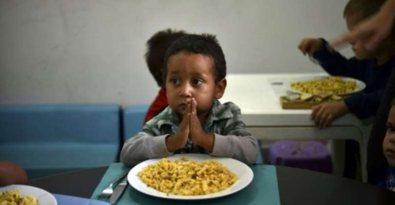 A child prays before eating at the Kapuy Foundation shelter which supports children abandoned, or with serious health problems, including undernourishment in Venezuela.  By YURI CORTEZ (AFP/File)