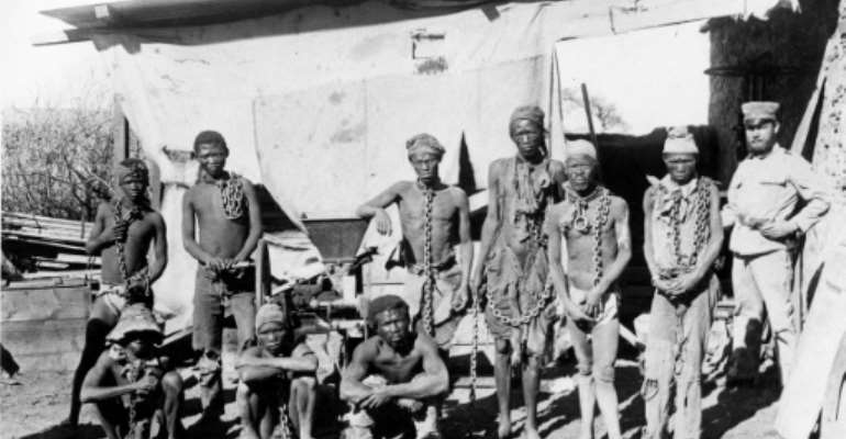 A colonial soldier (R) in German South West Africa (now Namibia) keeps a watchful eye over prisoners taken during the 1904-1908 war against the Herero and Nama people.  By Handout (NATIONAL ARCHIVES OF NAMIBIA/AFP/File)