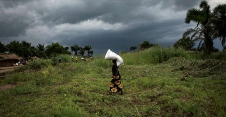 A Congolese woman carries a sack of food onto her heads at a food distribution on October 25, 2017 in Kasala, in the restive region of Kasai, central Democratic Republic of Congo.  By JOHN WESSELS (AFP/File)