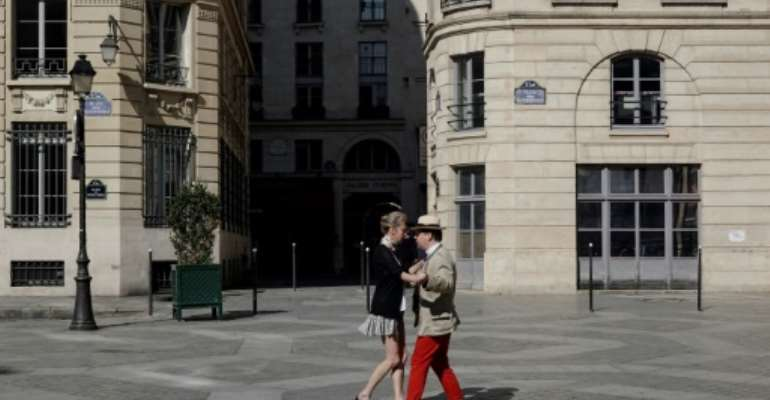 A couple dance in a empty square in downtown Paris on day 23 of a lockdown that is expected to be extended past the original deadline of April 15, 2020.  By Stefano RELLANDINI (AFP)
