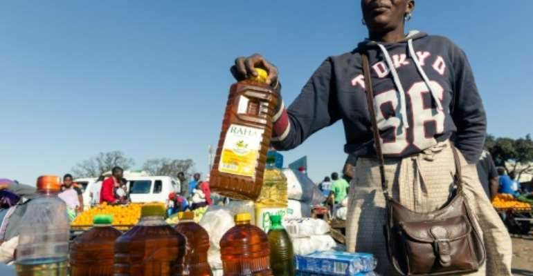 A customer buys cooking oil at a stall where smaller than standard measures of cooking oil is sold at Harare Mbare Musika marketplace as inflation sends food prices soaring.  By Jekesai NJIKIZANA (AFP)