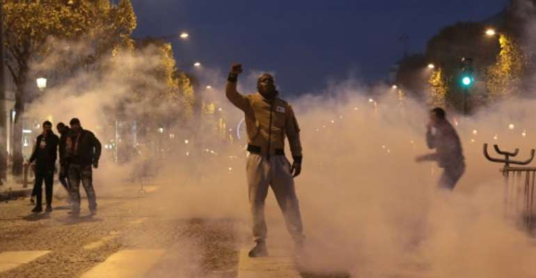 A demonstrator, standing through the smoke from tear gas, raises his fist during a march against