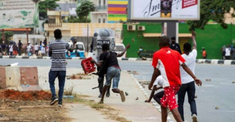 A demonstrator throws a rock at police office during the protests in Luanda on October 24.  By Osvaldo Silva (AFP)