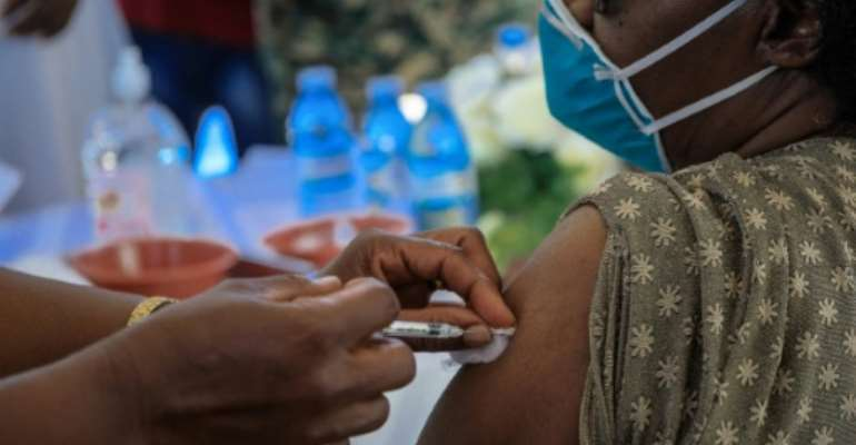 A doctor receives Uganda's first dose of Oxford/AstraZeneca vaccine on March 10. Shortages of the jab have led to a scam..  By Badru KATUMBA (AFP/File)