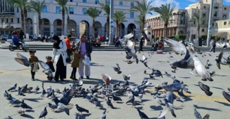 A family feeds pigeons in Libya's capital Tripoli on Tuesday, as politicians discussed the future structures of government in a bid to build peace in the long-troubled nation.  By Mahmud TURKIA (AFP)
