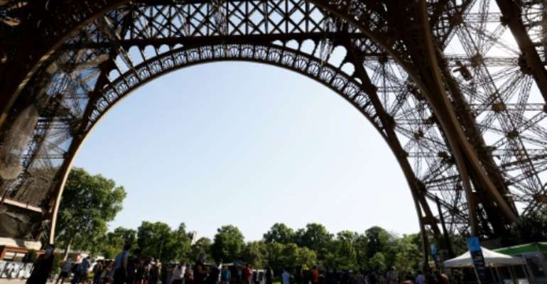 A few dozen tourists braved scorching heat in Paris to climb the Eiffel Tower's iron stairs.  By Thomas SAMSON (AFP)