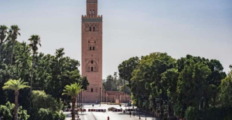 A few people walk by next to the Kutubiyya mosque's minaret tower at the Jemaa el-Fna square in the Moroccan city of Marrakesh on September 8, 2020, currently empty of its usual crowds due to the COVID-19 pandemic.  By FADEL SENNA (AFP)