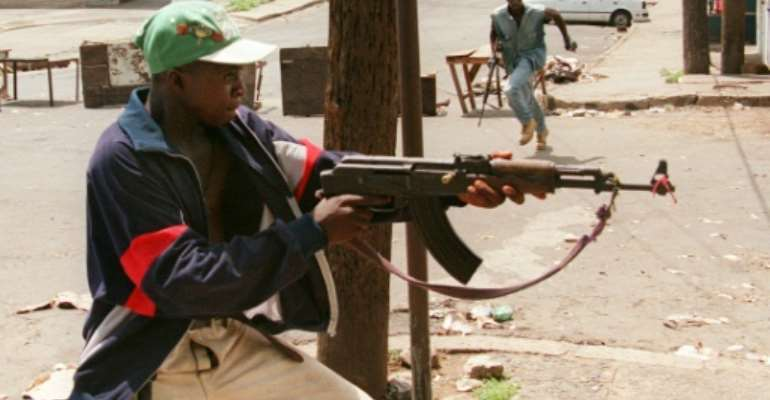 A fighter with Charles Taylor's NPFL fires at rivals from the United Liberation Movement of Liberia for Democracy (ULIMO) during Liberia's civil war in May 1996.  By CHRISTOPHE SIMON (AFP/File)