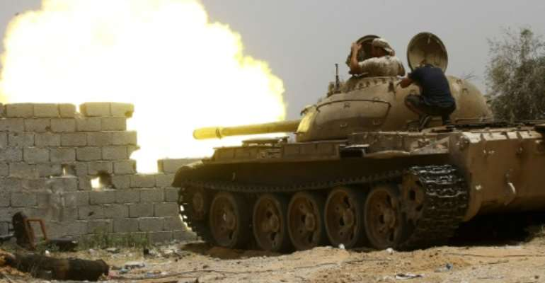 A file photo from June 2019 shows fighters loyal to the UN-recognised Government of National Accord (GNA) open tank fire south of the Libyan capital Tripoli during clashes with forces loyal to strongman Khalifa Haftar.  By Mahmud TURKIA (AFP/File)