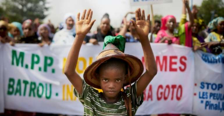 A Fulani boy protests in front of a sign saying 'Stop the Genocide' during a silent march in Bamako on June 30.  By MICHELE CATTANI (AFP)