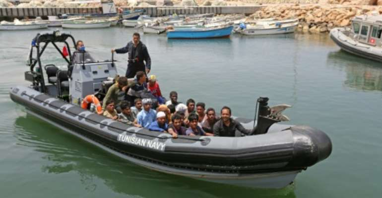 A group of migrants rescued by Tunisia's national guard during an attempted crossing of the Mediterranean by boat arrive at the port of el-Ketef in Ben Guerdane in southern Tunisia near the border with Libya.  By FATHI NASRI (AFP)