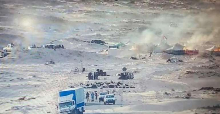 A handout picture published by the Royal Moroccan Army Facebook page on November 13, 2020, shows tents used by the Polisario Front ablaze near the Mauritanian border in Guerguerat after a military operation by Morocco.  By - (AFP)
