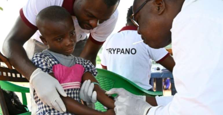 A health worker takes blood from a child in the Ivorian village of Paanenefla -- the sample will be tested for sleeping sickness.  By ISSOUF SANOGO (AFP)