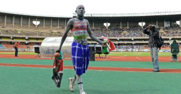 A Kenyan football fan walks on the pitch before an international match at Kasarani stadium in Nairobi.  By CARL DE SOUZA (AFP/File)
