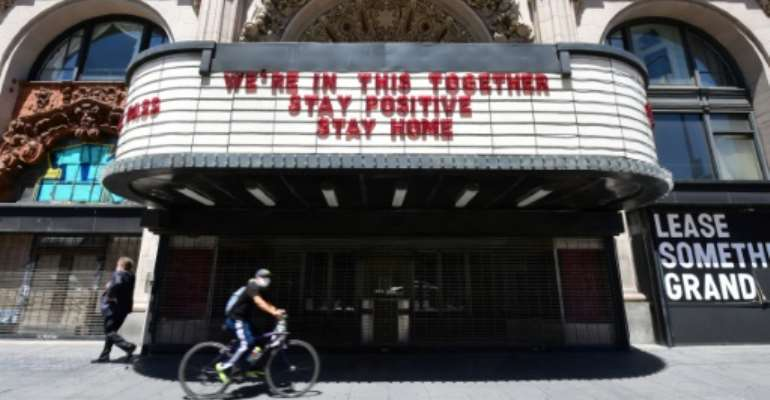 A Los Angeles cyclist in a face mask rides past the Million Dollar Theater, closed due to the coronavirus pandemic, with words on the marqee calling for togetherness.  By Frederic J. BROWN (AFP)