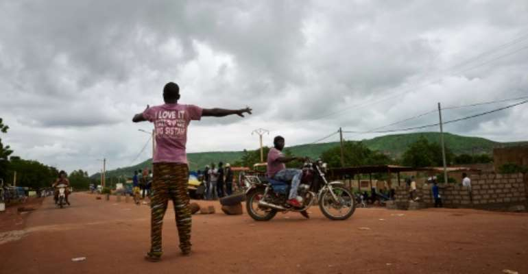 A Malian activist directs traffic on August 27, with the main road between the capital of Bamako and the western city of Kayes closed due to protest.  By MICHELE CATTANI (AFP/File)