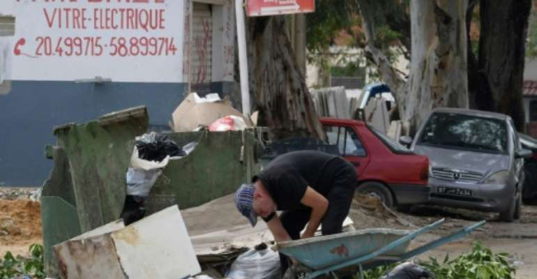 A man collects recyclable items in the impoverished Tunis suburb of Ettadhamen where unemployment is around 18 percent compared to a nationwide level of 15 percent.  By FETHI BELAID (AFP)