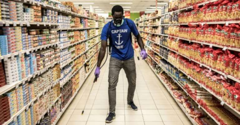A man disinfects an empty supermarket in Dakar.  By JOHN WESSELS (AFP)