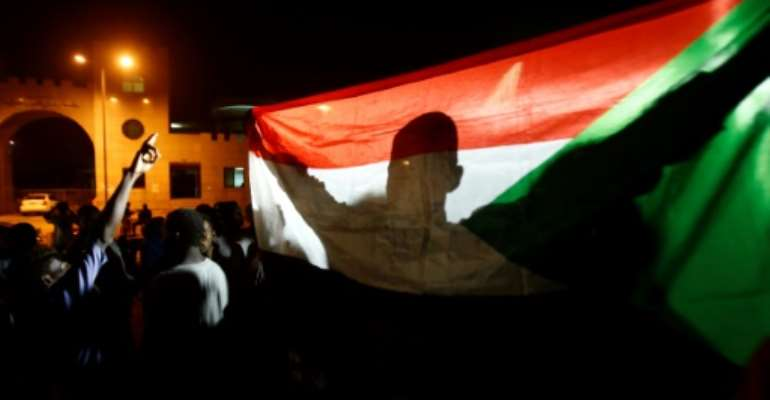 A man holds the Sudanese flag during a night-time demonstration outside the army headquarters in Khartoum on May 30, 2019.  By ASHRAF SHAZLY (AFP/File)