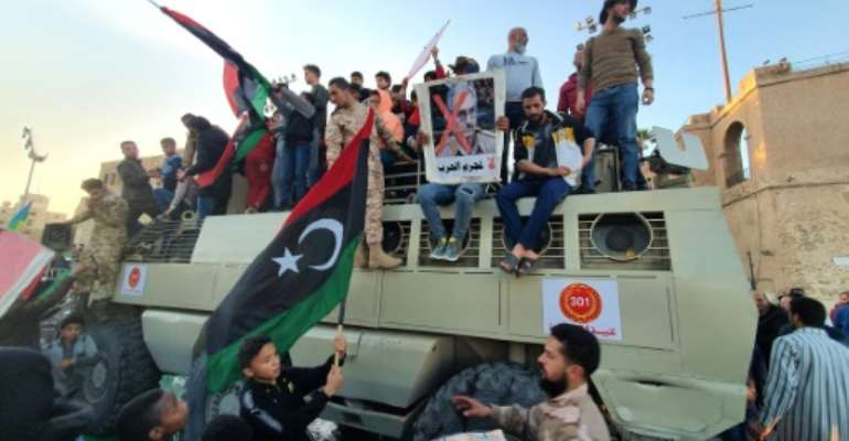 A man holds up a sign showing the face of Libyan strongman Khalifa Haftar crossed out with a red