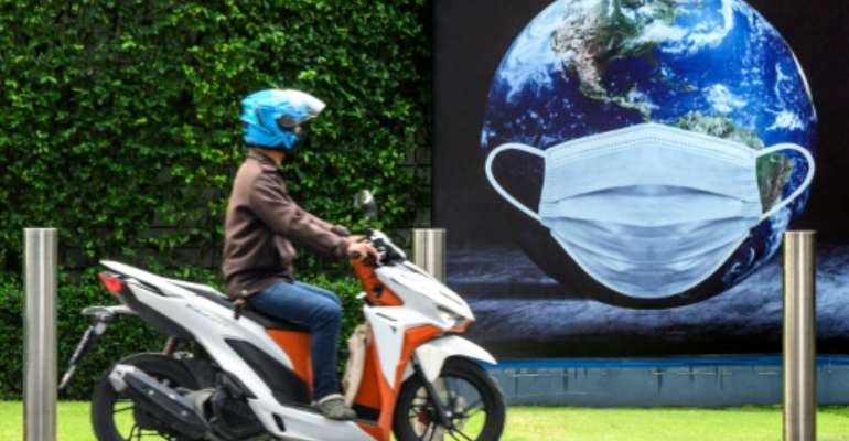 A man rides his scooter in front of a COVID-19 coronavirus related poster  in Bangkok.  By Mladen ANTONOV (AFP)