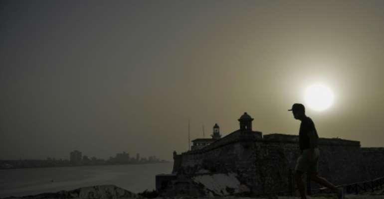 A man walks near Morro Castle as a vast cloud of Sahara dust blankets Havana.  By YAMIL LAGE (AFP)