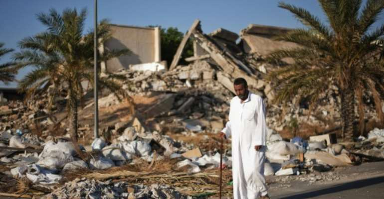 A man walks past a destroyed building at Libyan dictator Moamer Kadhafi's former headquarters in Tripoli in a picture taken in 2012, one year after the ruler was ousted and killed in a NATO-backed uprising.  By GIANLUIGI GUERCIA (AFP/File)