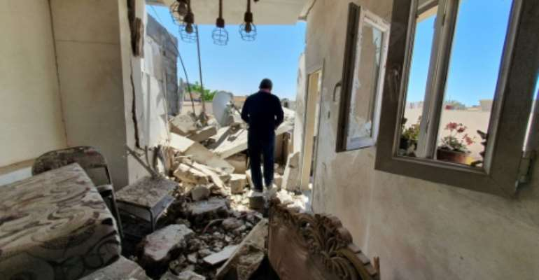 A man walks through the rubble of a building that was damaged when strongman Khalifa Haftar's forces shelled the neighborhood in the Libyan capital Tripoli on May 1, 2020 -- Hafter has been receiving help from Russian mercenaries, a UN report says.  By Mahmud TURKIA (AFP/File)