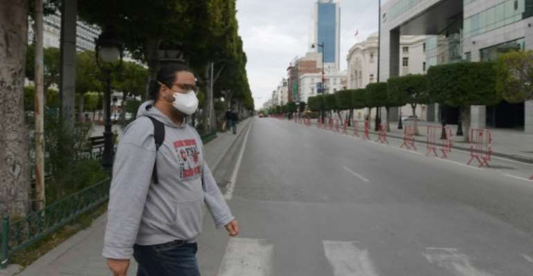 A man wears a face mask to protect against the COVID-19 disease in the Tunisian capital Tunis, where a curfew has already been imposed to stem the spread of the virus.  By FETHI BELAID (AFP/File)