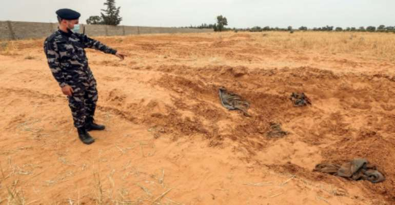 A member of security forces affiliated with the GNA's Interior Ministry surveyed the reported site of a mass grave in the town of Tarhuna, southeast of the capital Tripoli.  By Mahmud TURKIA (AFP)
